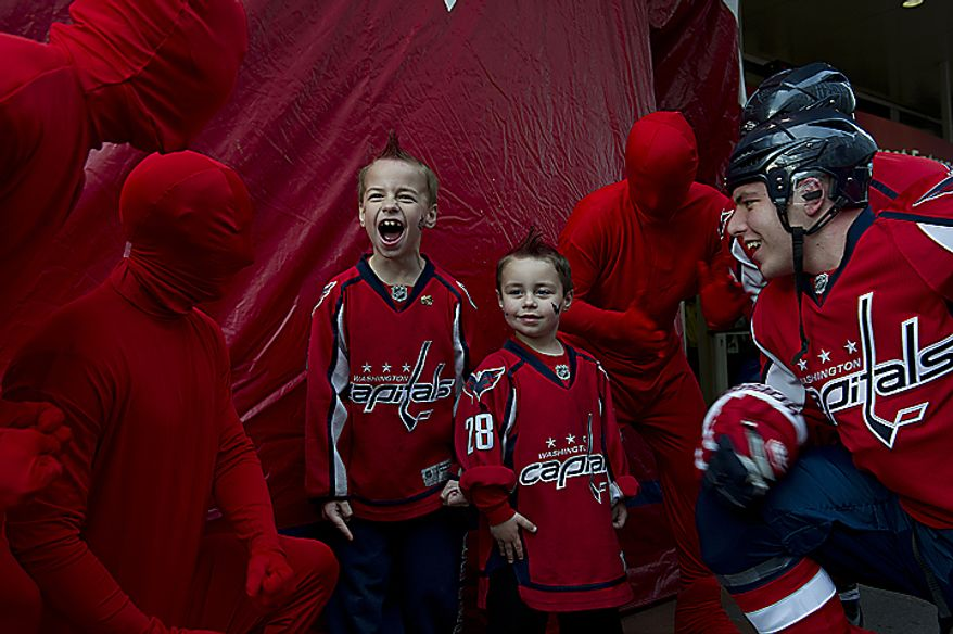 """Ashton (left), 7, and Riley Gresty of Edgewater, Md., get pumped up by """"The Red Men"""" outside the Verizon Center before the first Washington Capitals playoff game on Wednesday, April 13, 2011, in Washington. (Barbara L. Salisbury/The Washington Times)"""