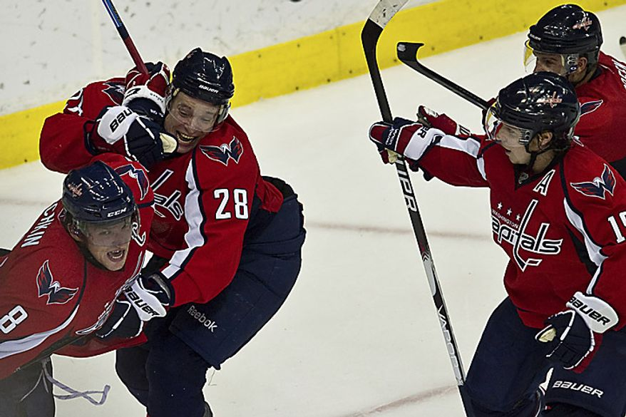 Teammates mob Capitals forward Alex Ovechkin after he scored a goal to tie the game at 1-1 during the third period of a playoff match against the New York Rangers at the Verizon Center in Washington on Wednesday, April 13, 2011. (Drew Angerer/The Washington Times)