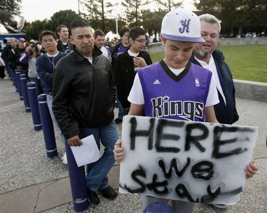 Fan Lisa McKee waits to enter the arena in front of images of current Sacramento Kings players before an NBA basketball game between the Kings and the Los Angeles Lakers in Sacramento, Calif., Wednesday, April 13, 2011. (AP Photo/Marcio Jose Sanchez)