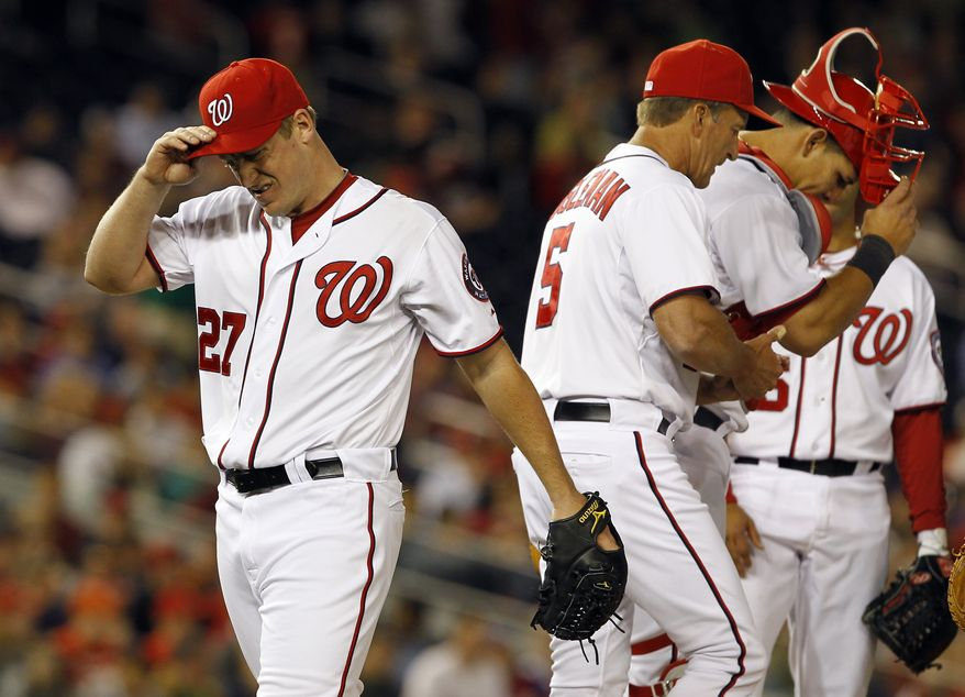 Washington Nationals pitcher Jordan Zimmerman, left, reacts as he relieved by manager Jim Riggleman, center, during the seventh inning of a baseball game with the Philadelphia Phillies at Nationals Park on Thursday, April 14, 2011 in Washington. The Phillies won 4-0.(AP Photo/Alex Brandon)