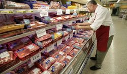 Meat department manager Kevin Morlan arranges packages of pork at a Dahl's grocery store in Des Moines, Iowa, on March 3, 2011. (AP Photo/Charlie Neibergall)