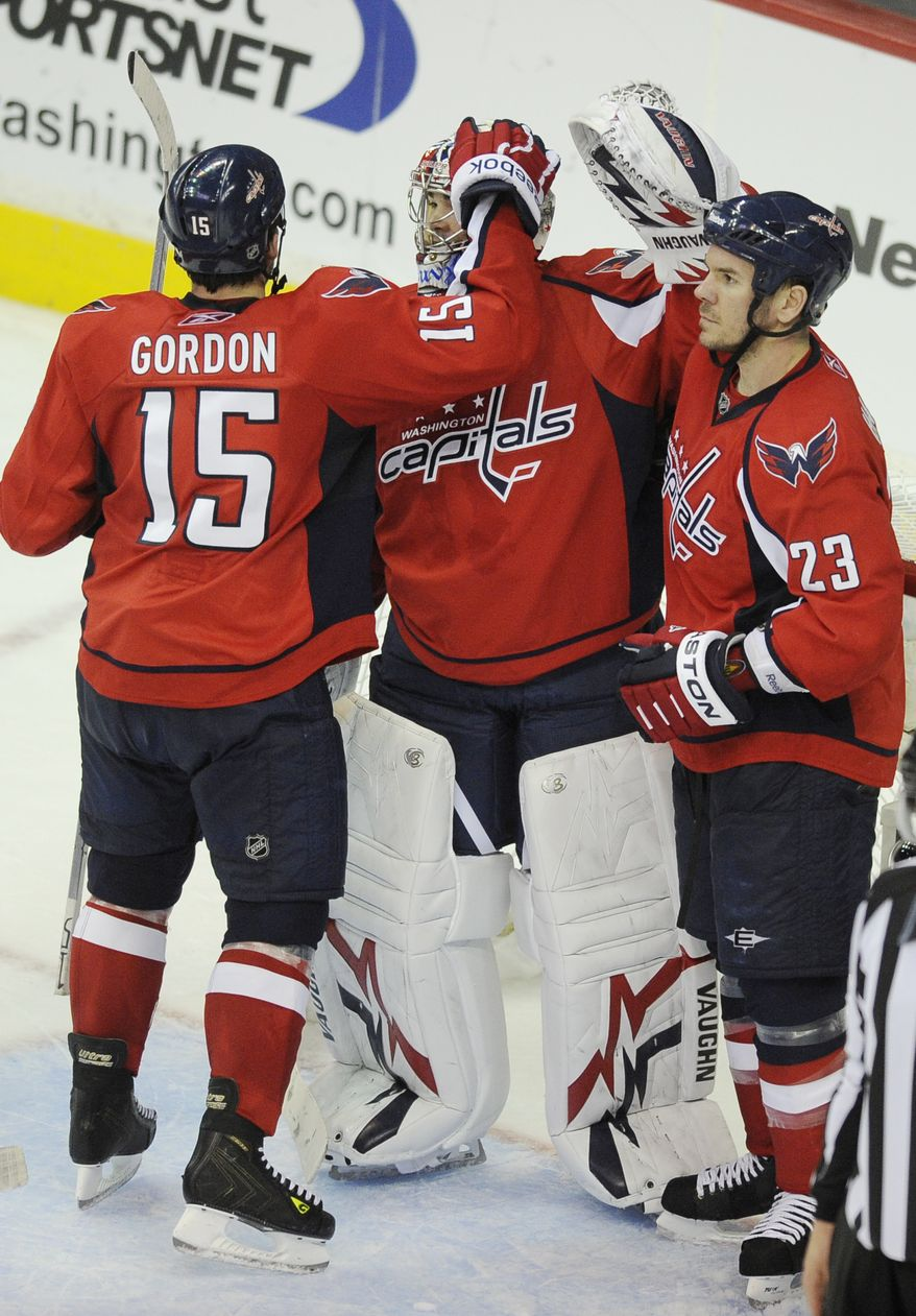 Washington Capitals right wing Boyd Gordon (15) celebrates teammates with Michal Neuvirth, center, of the Czech Republic, and Scott Hannan (23) after a 2-0 win over the New York Rangers in Game 2 of a first-round NHL Stanley Cup hockey playoff series on Friday, April 15, 2011, in Washington. (AP Photo/Nick Wass)