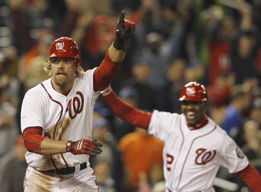 Washington Nationals baserunner Jayson Werth, left, reacts after scoring the winning run with third base coach Bo Porter at right, during the tenth inning of a baseball game with the Milwaukee Brewersat Nationals Park on Friday, April 15, 2011 in Washington. The Nationals won 4-3 in 10 innings. (AP Photo/Alex Brandon)