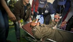 An ill evacuee is treated by aid workers while being moved to a waiting ambulance, as nearly 1,200 migrant workers who were evacuated from Misrata by boat, many suffering from dehydration and needing medical attention, arrived at the port in Benghazi, Libya, Friday, April 15, 2011. (AP Photo/Ben Curtis)