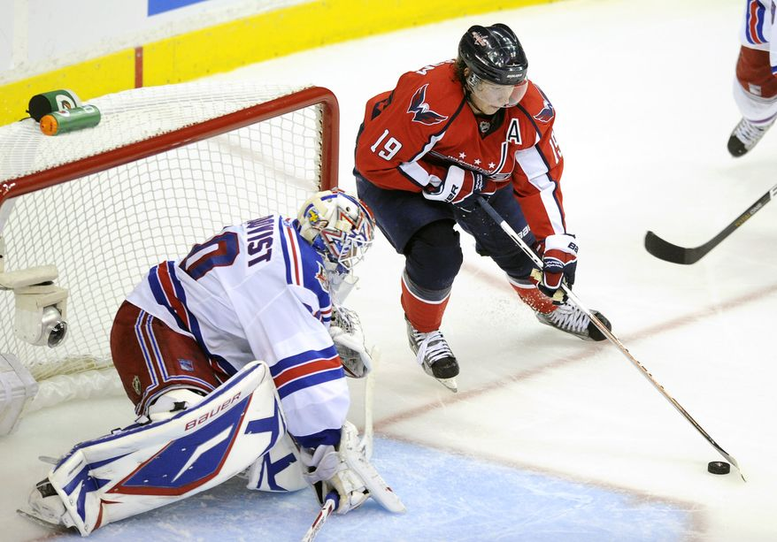 Washington Capitals center Nicklas Backstrom (19), of Sweden, brings the puck in front of New York Rangers goalie Henrik Lundqvist, left, also of Sweden, during the third period in Game 2 of a first-round NHL Stanley Cup hockey playoff series on Friday, April 15, 2011, in Washington. (AP Photo/Nick Wass)