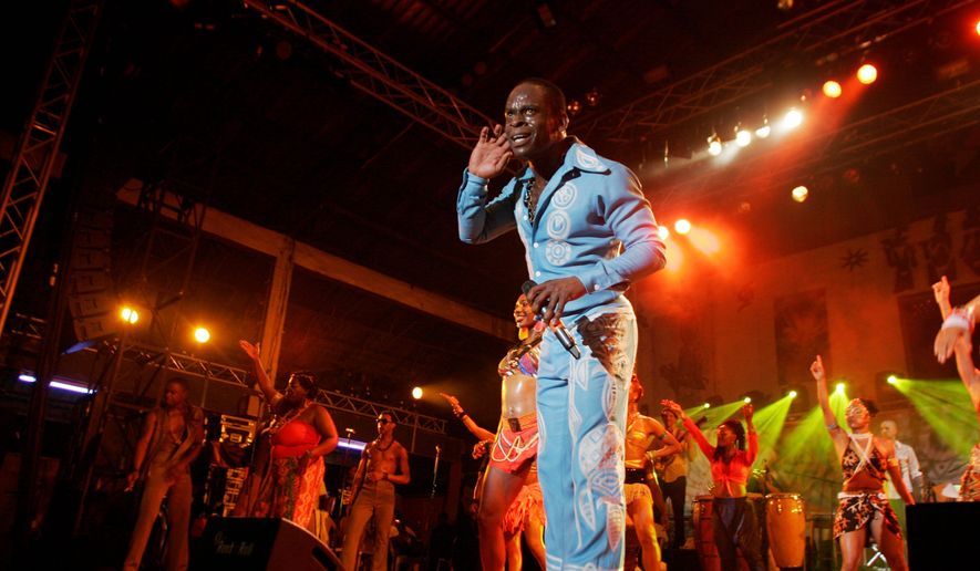 "Sahr Ngaujah, portraying the late Fela Anikulapo-Kuti, performs at New Afrika Shrine in Lagos, Nigeria, on Thursday after the ensemble cast from the Tony award-winning ""Fela!"" brought the Broadway production to the native country of the Afrocbeat superstar for a series of performances. Audiences saw the musical in a concert space run by the star's son Femi and daughter Yeni. The New Afrika Shrine is a relocated version of the place where their father once played, which later burned down. (Associated Press)"