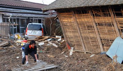 Kizuki Ishimori, 27, clears debris from his family's home in Higashi-Matsushima. After the March 11 tsunami devastated his hometown, Mr. Ishimori said he might have to move south to find work. (Christopher Johnson/Special to The Washington Times)