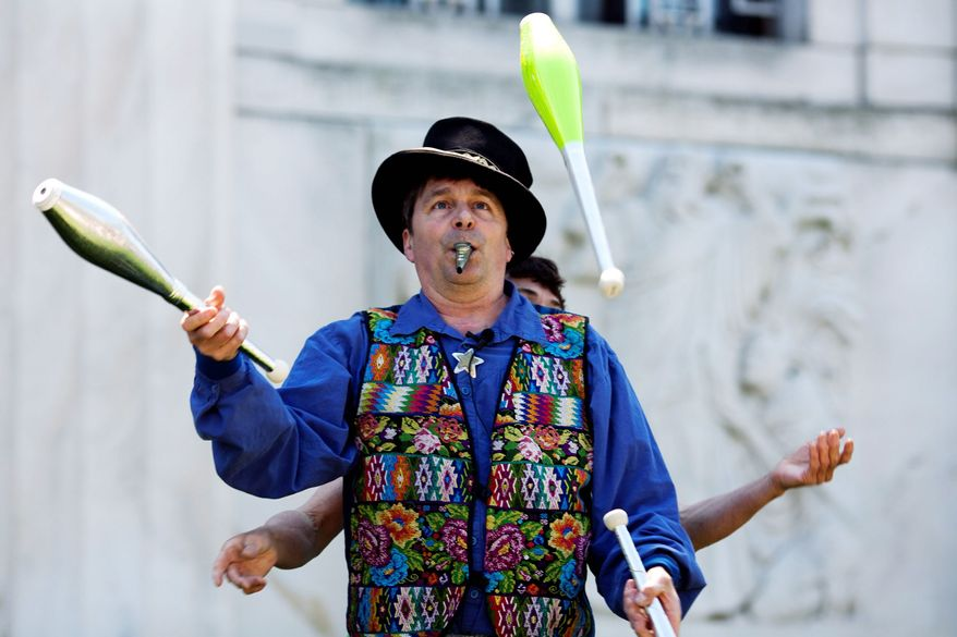 Jester and entertainer Nick Newlin juggles for visitors at Shakespeare's birthday celebration. (Drew Angerer/The Washington Times)
