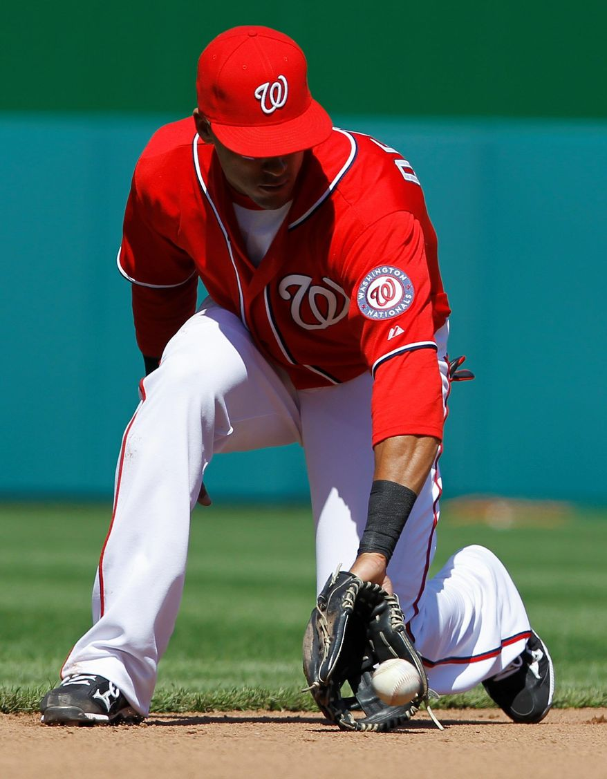 ASSOCIATED PRESS Washington Nationals shortstop Ian Desmond grabs a ground ball hit by the Milwaukee Brewers' Casey McGehee during the fifth inning of the first game. Nats pitcher Jason Marquis scattered nine Brewers hits and two runs over seven innings.