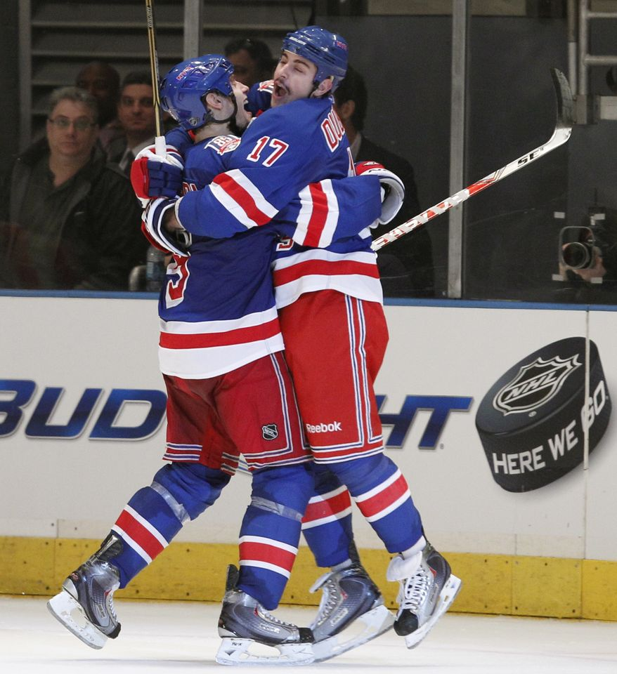 New York Rangers defenseman Dan Girardi (5), left, celebrates with left wing Brandon Dubinsky (17) after Dubinsky scored the winning goal against the Washington Capitals in the third period of Game 3 of a first-round NHL hockey Stanley Cup playoff series at Madison Square Garden in New York, Sunday, April 17, 2011. The Rangers defeated the Capitals 3-2. (AP Photo/Kathy Willens)