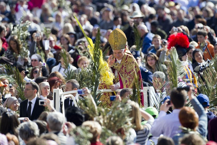 Pope Benedict XVI carries a palm branch as he arrives to celebrate Palm Sunday Mass in St. Peter's Square at the Vatican on Sunday, April 17, 2011. (AP Photo/Andrew Medichini)