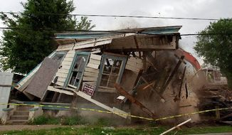"""** FILE ** In this 2011 file photo, one firm swipe from an excavator demolishes a New Orleans house damaged in Hurricane Katrina. Preservationists and HBO, which uses several such ramshackle houses in ads for """"Treme,"""" tried but failed to save them. (Associated Press)"""