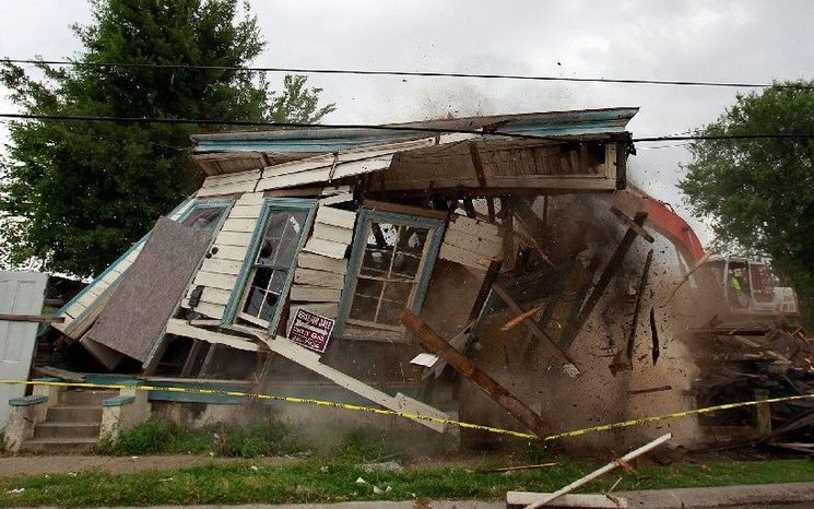 "** FILE ** In this 2011 file photo, one firm swipe from an excavator demolishes a New Orleans house damaged in Hurricane Katrina. Preservationists and HBO, which uses several such ramshackle houses in ads for ""Treme,"" tried but failed to save them. (Associated Press)"