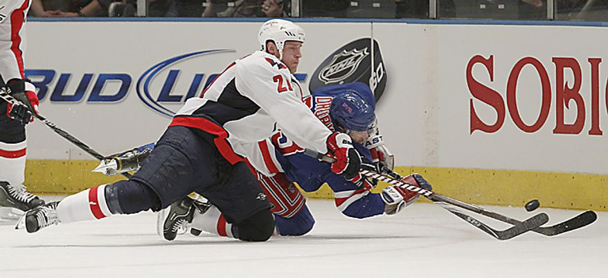 Washington Capitals center Brooks Laich (21) scuffles with New York Rangers left wing Chris Drury for control of the puck in the first period of Game 3 of a first-round NHL Stanley Cup playoff series at Madison Square Garden in New York, Sunday, April 17, 2011.  (AP Photo/Kathy Willens)