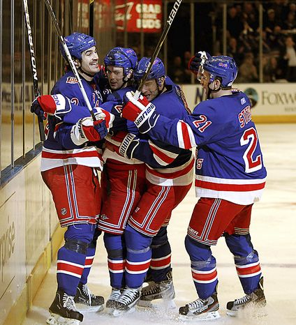New York Rangers center Brian Boyle (left), left wing Wojtek Wolski (second from right) and center Derek Stepan (21) celebrate with center Erik Christensen (second from left) after Christensen scored against the Washington Capitals in the second period of Game 3 of a first-round NHL Stanley Cup playoff series at Madison Square Garden in New York, Sunday, April 17, 2011. (AP Photo/Kathy Willens)