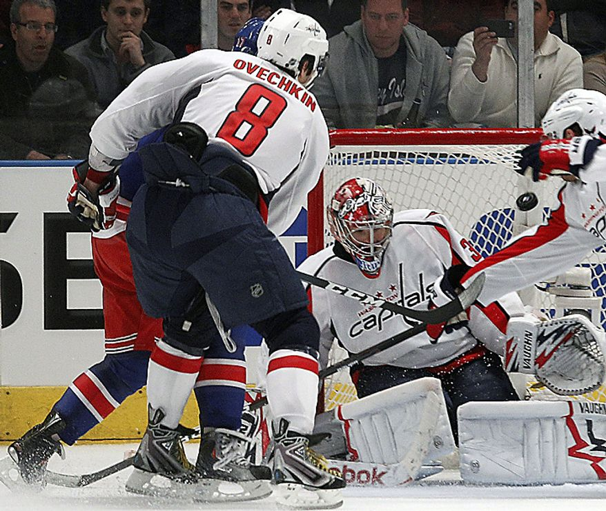 Washington Capitals left wing Alex Ovechkin (8) watches as Brandon Dubinsky's (back left) game-winning shot flies over the left shoulder of Washington Capitals goalie Michal Neuvirth in the third period of the New York Rangers' 3-2 victory in Game 3 of their first-round NHL Stanley Cup playoff series at Madison Square Garden in New York, Sunday, April 17, 2011. (AP Photo/Kathy Willens)