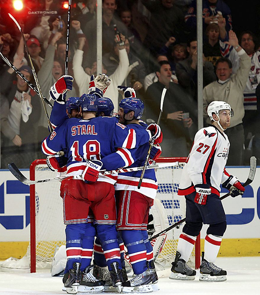 New York Rangers celebrate Vinny Prospal's third-period goal as Washington Capitals defenseman Karl Alzner (27) skates away during Game 3 of their first-round NHL Stanley Cup playoff series at Madison Square Garden in New York, Sunday, April 17, 2011. The Rangers won 3-2. (AP Photo/Kathy Willens)