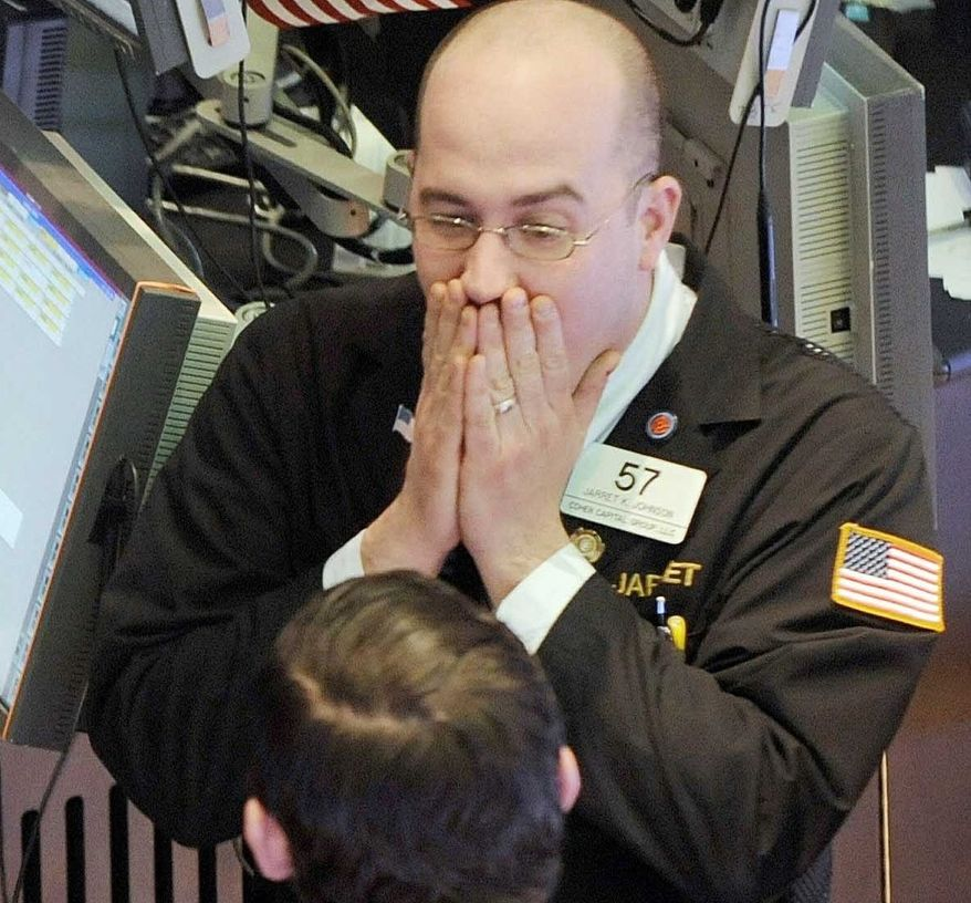 STOCK SHOCK: Jarrett Johnson (top) of Cohen Capital Group talks to fellow traders Monday at the New York Stock Exchange. Stocks plunged after S&P's credit warning. (Associated Press)