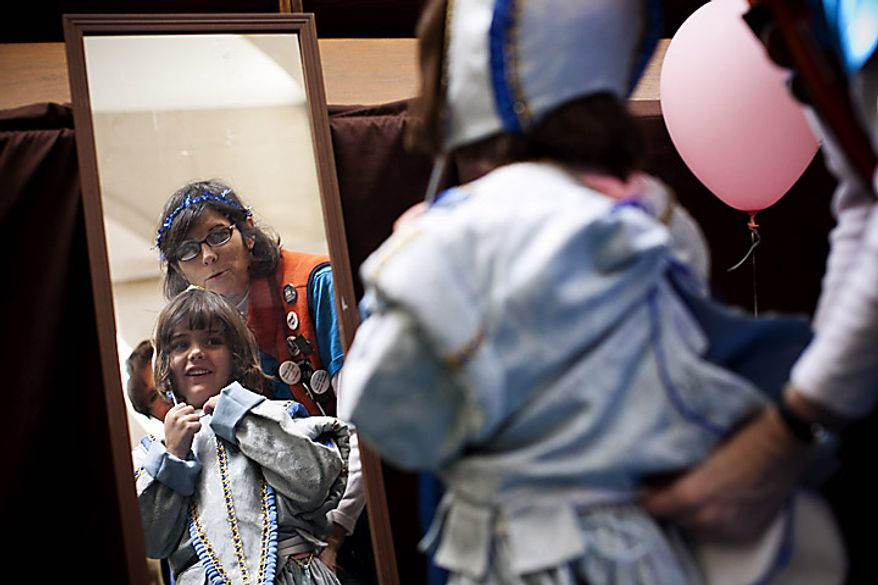 Katie Murphy, 5, of Arlington, tries on Renaissance era clothing with the help of Folger Senior Docent Grace Schiraldi during an open house for Shakespeare's Birthday at the Folger Shakespeare Library, in Washington, D.C., Sunday, April 17, 2011. (Drew Angerer/The Washington Times)