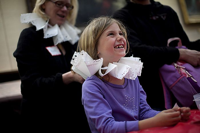 """Lark Goodson,7, of the District, gets help from volunteer Heidi Keller as she puts on a Renaissance era """"ruff"""" she made during an open house for Shakespeare's Birthday at the Folger Shakespeare Library, in Washington, D.C., Sunday, April 17, 2011. Ruffs were popular in the 1580s to 1590s. (Drew Angerer/The Washington Times)"""
