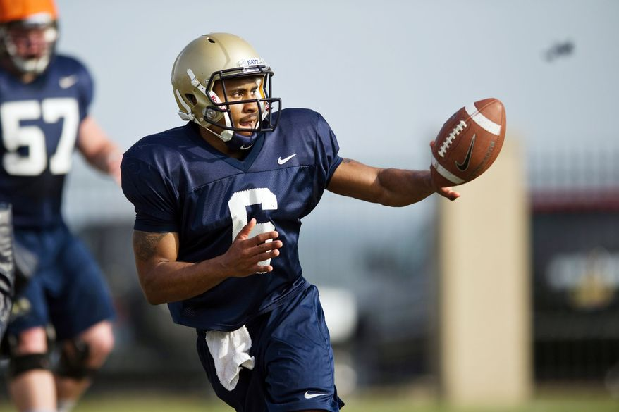 Navy's backup quarterbacks Trey Miller (seen here) and Jarvis Cummings try to perfect option pitches during spring practice at Rip Miller Park at the Naval Academy in Annapolis. The sophomores are vying for the No. 2 spot behind starter Kriss Proctor when games start in September. (Drew Angerer/The Washington Times)