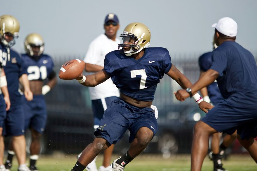 Navy's backup quarterbacks Jarvis Cummings (seen here) and Trey Miller try to perfect option pitches during spring practice at Rip Miller Park at the Naval Academy in Annapolis. The sophomores are vying for the No. 2 spot behind starter Kriss Proctor when games start in September. (Drew Angerer/The Washington Times)