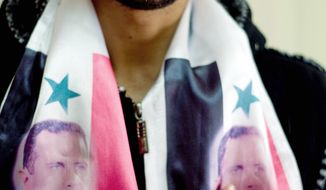 Arab Druse Imad Merei wears a scarf with the portrait of Syrian President Bashar Assad at his house in the village of Majdal Shams in the Golan Heights.