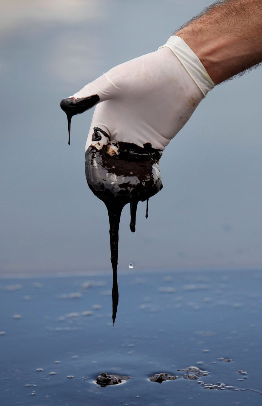 A member of Louisiana Gov. Bobby Jindal's staff reaches into thick oil on the surface of the northern regions of Barataria Bay in Plaquemines Parish, La., in April 2010. Environmental activists predict it will be a long time before the full extent of the spill's impact on Gulf wetlands can be determined. (Associated Press)