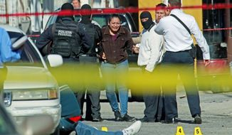 A woman sees a relative lying dead on the ground after he was killed by gunmen in Ciudad Juarez, Mexico, in December 2010. (Associated Press)