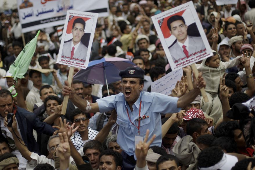 A Yemeni police officer holding posters of a demonstrator killed by security forces last March, shouts slogans during a demonstration by anti-government protestors demanding the resignation of Yemeni President Ali Abdullah Saleh, in Sanaa, Yemen, on Sunday, April 10, 2011. (AP Photo/Muhammed Muheisen)