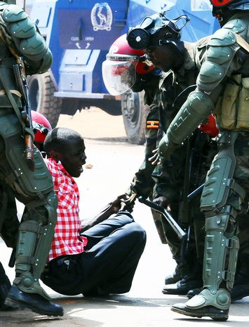 """Ugandan military police arrest a demonstrator during Monday's """"walk to work"""" protest against the high cost of fuel and food in Kampala. The same day, police arrested Kizza Besigye, the country'"""