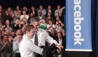 **FILE** President Obama and Facebook CEO Mark Zuckerberg take off their jackets at Facebook headquarters in Palo Alto, Calif., on April 20, 2011, before their joint town-hall meeting to discuss reducing the federal deficit. (Associated Press)