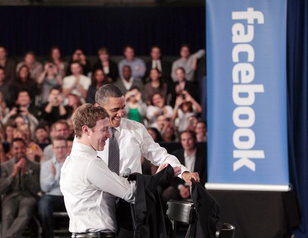 **FILE** President Obama and Facebook CEO Mark Zuckerberg take off their jackets at Facebook headquarters in Palo Alto, Calif., on April 20, 2011, before their joint town-hall meeting to discuss reducing
