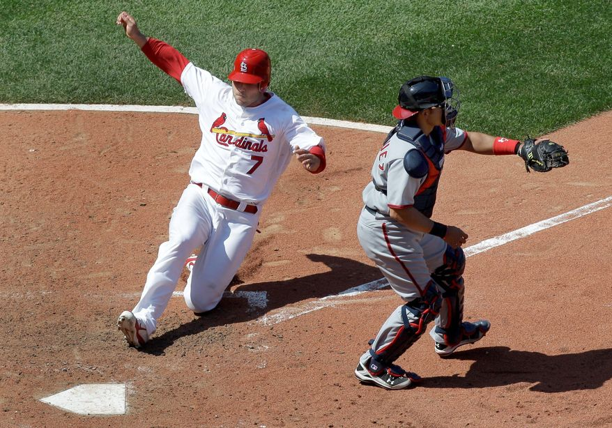 St. Louis Cardinals' Matt Holliday scores on a double by David Freese as Washington Nationals catcher Ivan Rodriguez waits for the late throw during the eighth inning of Thursday's game, which the Cards won 5-0. (Associated Press)