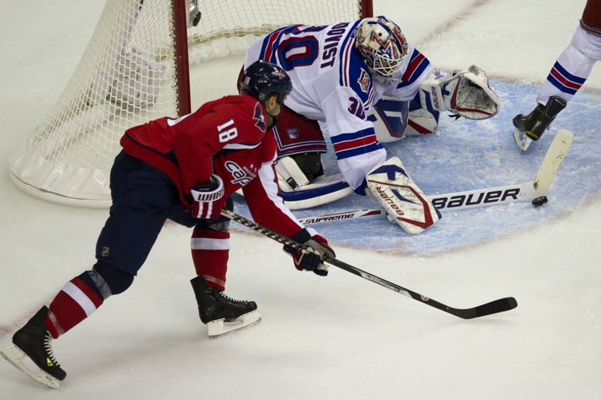 Capitals Marco Sturm fights for the puck as Rangers goalie Henrik Lundqvist sweeps it away from the goal during the first period of game five of the first round playoff series, at the Verizon Center in Washington, D.C., Saturday, April 23, 2011. (Drew Angerer/The Washington Times)