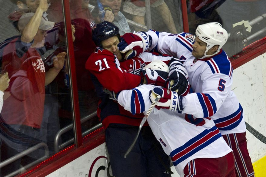 Capitals Brooks Laich takes a punch to the face from Rangers Dan Giradi after the Caps scored in the first period during game five of the first round playoff series, at the Verizon Center in Washington, D.C., Saturday, April 23, 2011. (Drew Angerer/The Washington Times)