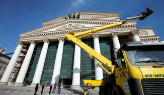 A construction crane is utilized outside the Bolshoi Theater in Moscow. The construction company says 3,500 workers are still busy adding sophisticated electronic and hydraulic devices, redesigning the stage floor to ease the ballet dancers' pain and completing an underground stage located just a short distance from a metro station. (Associated Press)