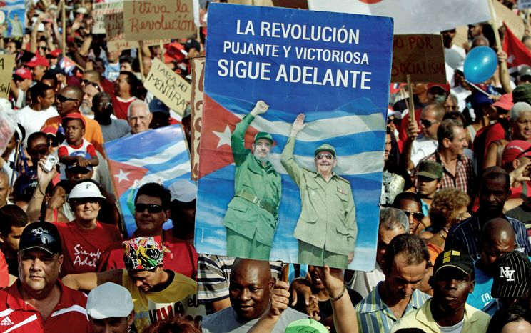 A man holds up a poster with images of Cuba's leader Fidel Castro and his brother, President Raul Castro, during the parade marking the 50th anniversary of the Bay of Pigs failed invasion in Havana on April 16. Some Cubans are anxious for a new generation of leaders to emerge. (Associated Press)