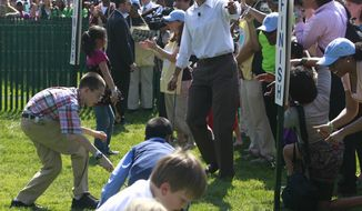 President Obama cheers on a group of children rolling their eggs toward the finish line at the annual White House Easter Egg Roll on April 25, 2011, on the South Lawn of the White House. (Associated Press)
