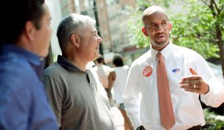 Robert Gordon (center), co-owner of the Red Velvet Cupcakery, chats Tuesday with interim D.C. Council member Sekou Biddle. Mr. Biddle was vying against several rivals Tuesday in a special election for a full term. (Nicholas Gingold/Special to The Washington Times)