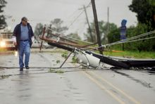 Allen Hartfield walks past downed electric lines on County Road 101 in Oxford, Miss., on Wednesday. A spate of severe storms downed trees, as well as power lines, with deadly effect in Mississippi. AP Photo/Oxford Eagle, Bruce Newman)