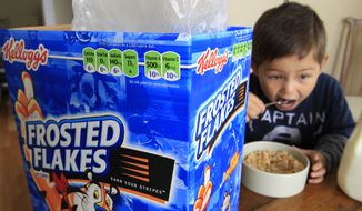 Nathaniel Donaker, 4, eats Kellogg's Frosted Flakes cereal at his home in Palo Alto, Calif., on Thursday. Commercials promoting sugary breakfast cereals could be put on a strict diet under government guidelines urging food companies to limit marketing of unhealthy products to children. Under a proposal announced Thursday by several government agencies, companies would be urged to only market foods to children ages 2 through 17 if they are low in fats, sugars and sodium and contain specified healthy ingredients. (Associated Press)