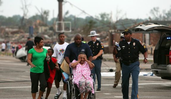 A misplaced family is assisted by emergency responders Wednesday, April 27, 2011, near in Tuscaloosa, Ala. A wave of severe storms laced with tornadoes strafed the South region. (AP Photo/Tuscaloosa News, Dusty Compton)