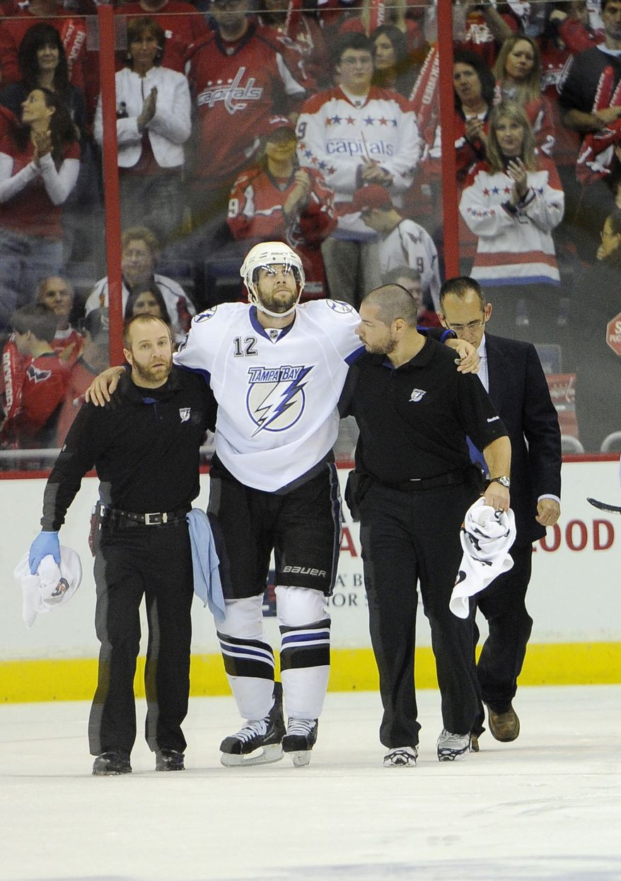 Tampa Bay Lightning left wing Simon Gagne (12) is helped off the ice after being injured during the first period in Game 1 of a conference semifinal NHL Stanley Cup hockey playoff series against the Washington Capitals, Friday, April 29, 2011, in Washington. Tampa Bay won 4-2. (AP Photo/Nick Wass)