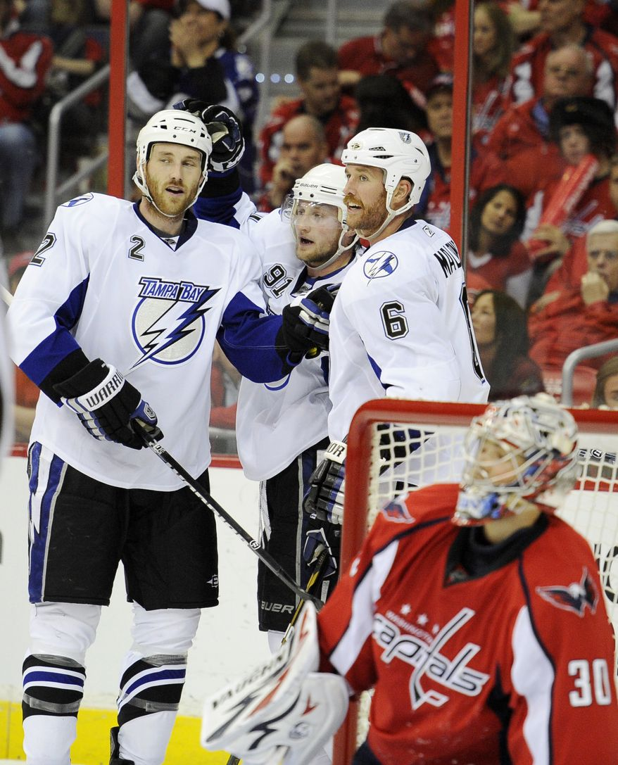 Tampa Bay Lightning center Steven Stamkos (91) celebrates his goal with Eric Brewer (2) and Ryan Malone (6) as Washington Capitals goalie Michal Neuvirth (30), from the Czech Republic, looks on during the second period in Game 1 of a conference semifinal NHL Stanley Cup hockey playoff series, Friday, April 29, 2011, in Washington. (AP Photo/Nick Wass)