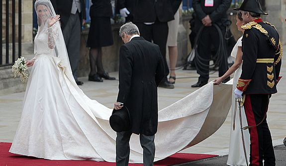 Kate Middleton, left, arrives for her wedding with Britain's Prince William as her maid of honour Pippa Middleton holds the train and Michael Middleton, Kate Middleton's father, front, looks on at Westminster Abbey at the Royal Wedding in London Friday, April 29, 2011. (AP Photo/Gero Breloer)