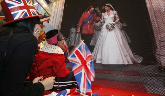 Hong Kong residents sit next to a giant TV screen showing the live broadcast of Britain's Prince William and Kate Middleton at Westminster Abbey for the Royal Wedding at a shopping mall in Hong Kong Friday, April 29, 2011.  (AP Photo/Kin Cheung)