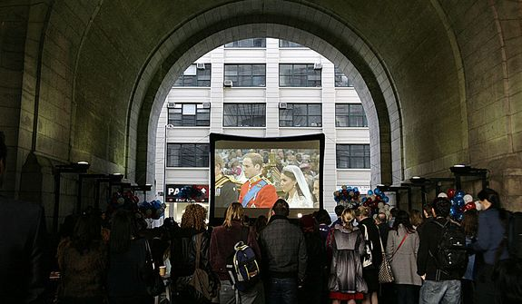 """A crowd watches the wedding ceremony of Britain's Prince William and Kate Middleton on a video screen under the Manhattan Bridge in the borough of Brooklyn in New York on April 29, 2011. Some 2 billion people across the globe were believed to have tuned in as the future king and queen of England started their lives as husband and wife with the two simple words """"I will."""" (AP Photo/Peter Morgan)"""