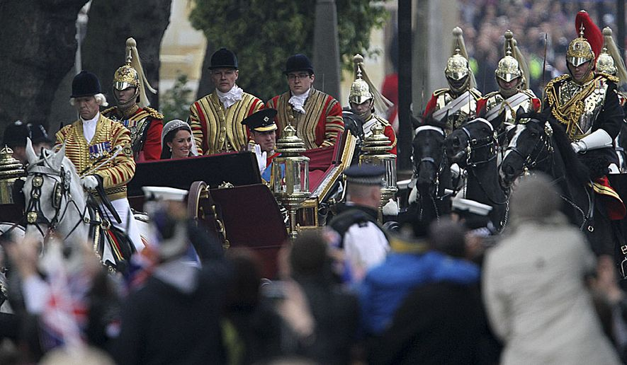 Britain's Prince William and his wife Kate, the Duchess of Cambridge make their way past the Parliament Buildings at the Royal Wedding in London Friday, April, 29, 2011. (AP Photo/Tim Hales)