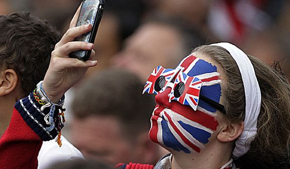 A spectator takes a photo outside of Westminster Abbey before the Royal Wedding of Prince William and Kate Middleton in London Friday, April, 29, 2011. (AP Photo/Gero Breloer)